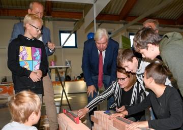 Bildungs-Landesrätin Christiane Teschl-Hofmeister, Bildungsdirektor Johann Heuras und Messedirektor Werner Roher mit Kindern beim Entwurf einer Ziegelmauer